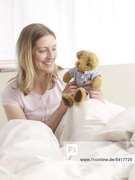 Frau mit Teddy im Bett