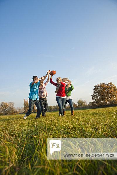Junge Leute spielen mit Football