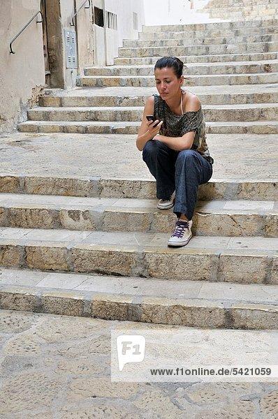 Stufe  Außenaufnahme  sitzend  Frau  Text  Kurznachricht  jung  freie Natur