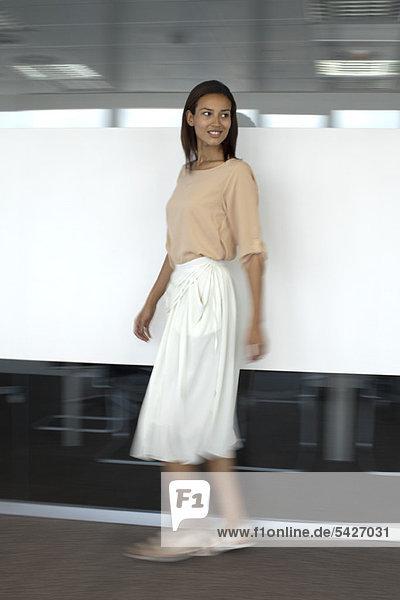 Woman walking in office  blurred motion
