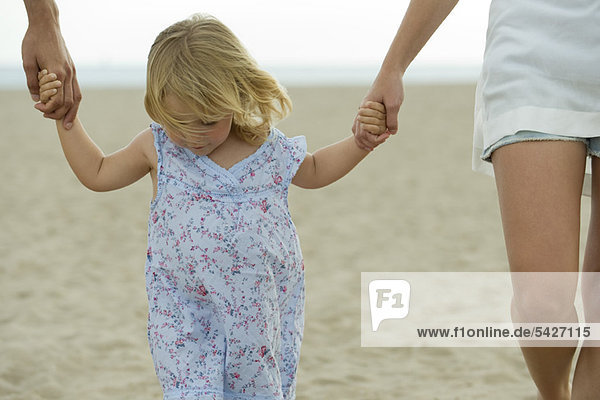 Little girl walking hand in hand with parents at the beach  cropped