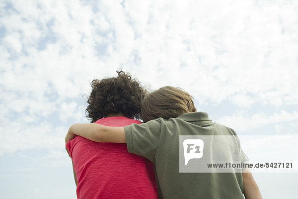 Junge Freunde sitzen Seite an Seite im Freien  Rückansicht