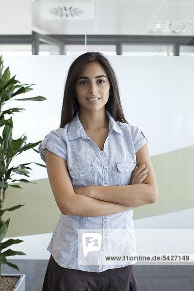 Lächelnde Frau im Büro mit gefalteten Armen  Portrait