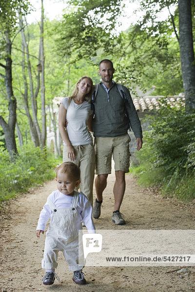 Kleinkind Mädchen beim Waldspaziergang mit den Eltern