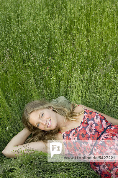 Young woman relaxing in tall grass  portrait