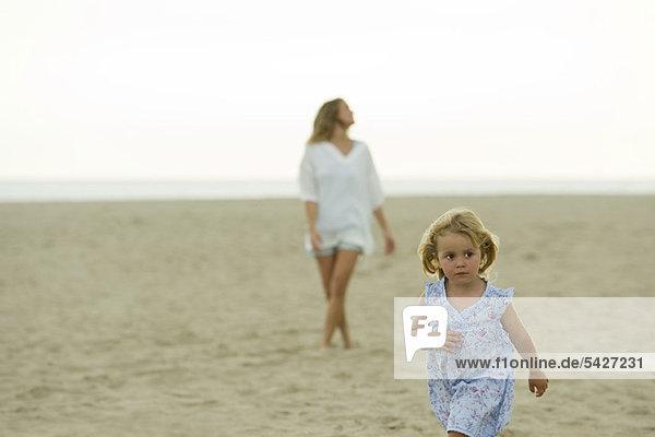 Kleines Mädchen  das am Strand spazieren geht