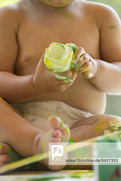 Baby spielt mit Farbe  abgeschnitten