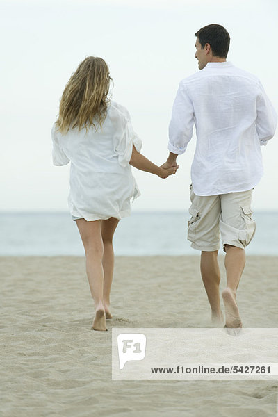 Couple walking together on beach  rear view