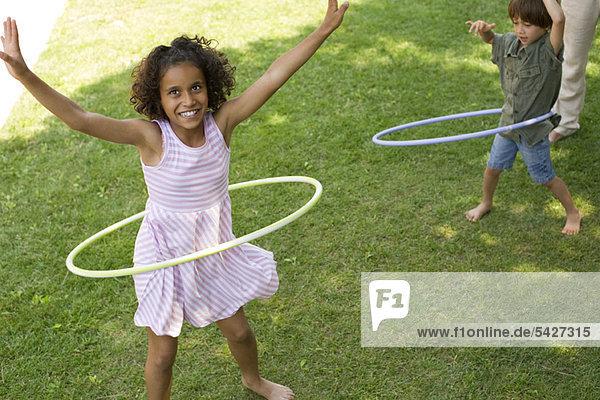 Kinder beim Spielen mit Kunststoffreifen im Freien