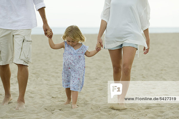 Little girl walking on beach with her parents  cropped