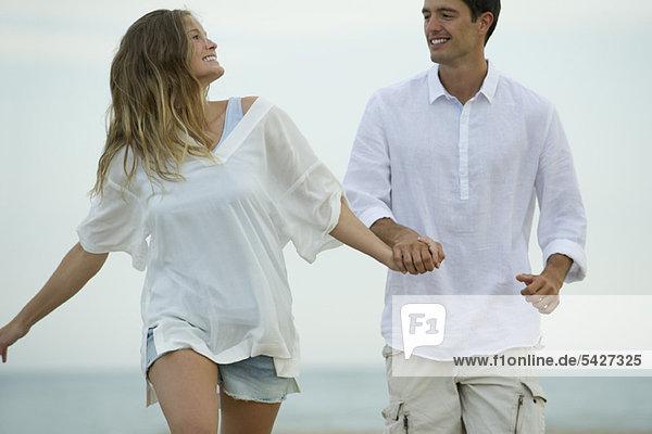 Paar geht Hand in Hand am Strand spazieren