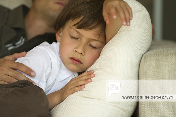 Boy napping on sofa with his father  cropped