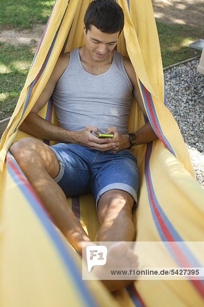 Man relaxing in hammock  text messaging with cell phone