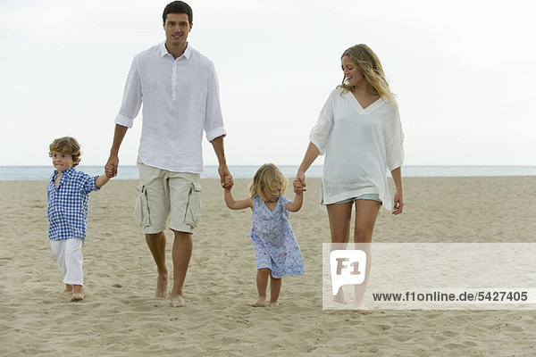 Family walking hand in hand at the beach