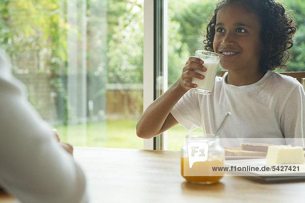 Girl drinking glass of milk at breakfast