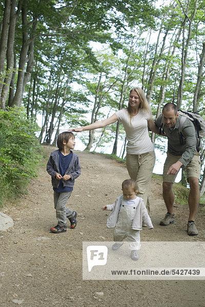 Eltern spielen mit Kindern im Wald