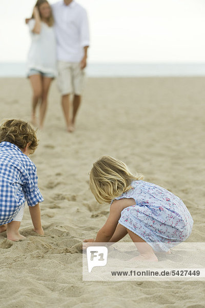 Children playing in sand at the beach