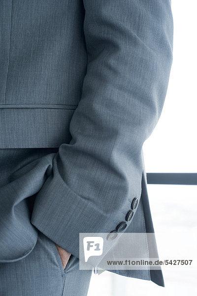 Executive mit Hand in der Tasche  beschnitten