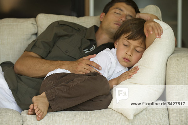 Father and son napping together on sofa