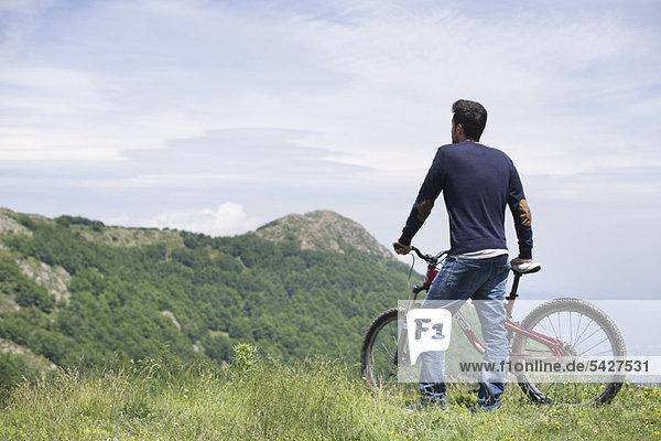 Mann steht am Mountainbike  genießt die Aussicht auf die Berge  Rückansicht