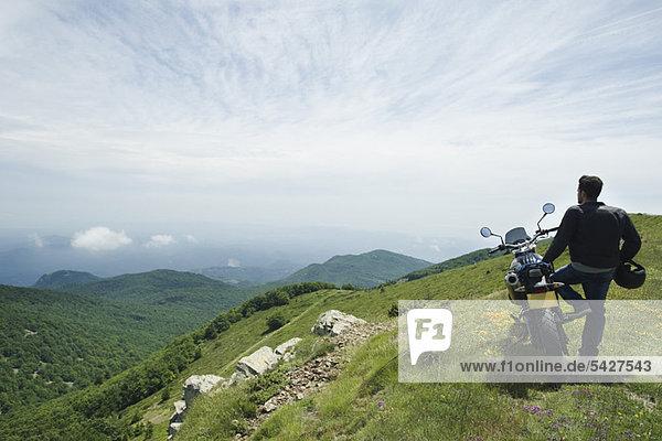 Mann steht mit dem Motorrad auf dem Berg  Rückansicht