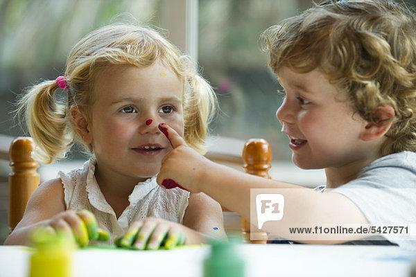 Kleiner Junge  der die Nase seiner Schwester bemalt.