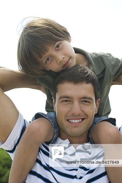 Boy riding on his father's shoulders  portrait