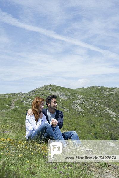 Paar auf der Wiese sitzend