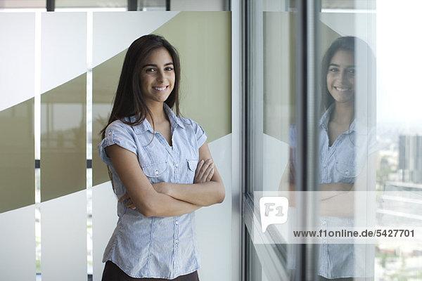 Lächelnde Frau am Fenster stehend mit gefalteten Armen