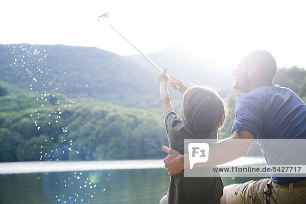 Father and son fishing  boy caught fish in fishing net