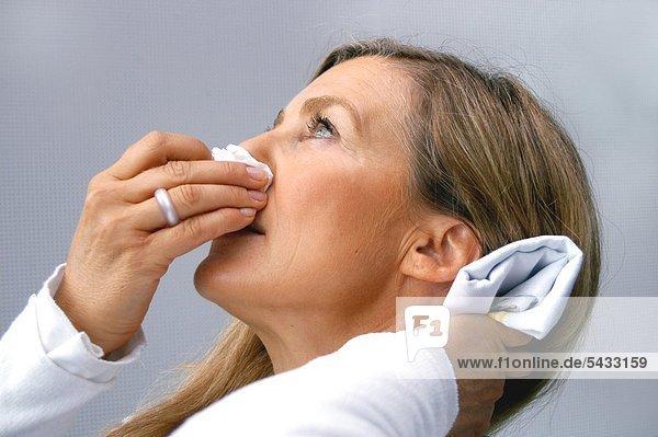 Frau mit Nasenbluten hält ihren Kopf zurück   Taschentuch an der Nase