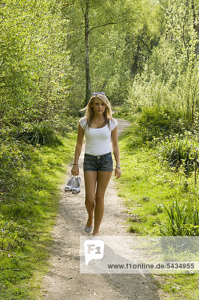 junges Mädchen geht barfuß im Wald spazieren