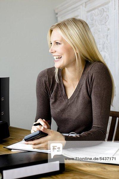 Fröhliche blonde Frau mit Taschenrechner