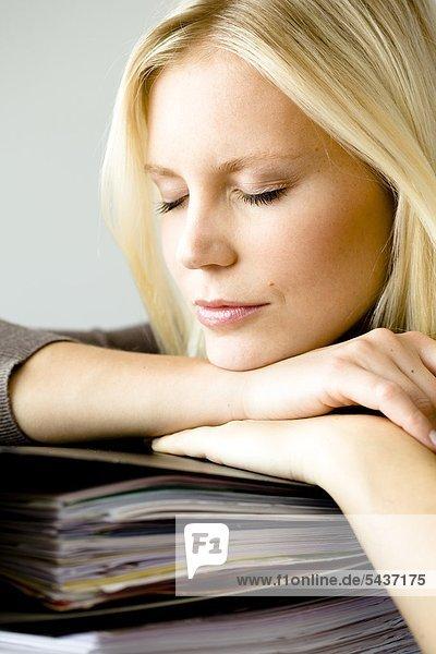 Blonde Frau mit geschlossenen Augen stützt sich auf Aktenordnern auf Blonde Frau mit geschlossenen Augen stützt sich auf Aktenordnern auf