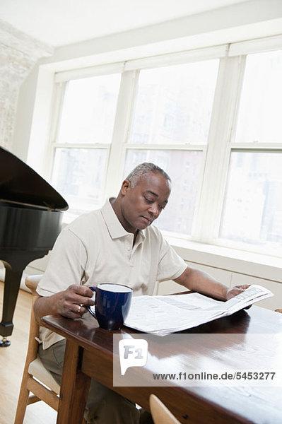Ein reifer Mann sitzt am Esstisch und liest eine Zeitung.