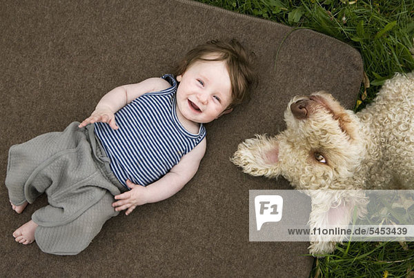 Ein kleines Mädchen und ein Hund liegen draußen. Ein kleines Mädchen und ein Hund liegen draußen.