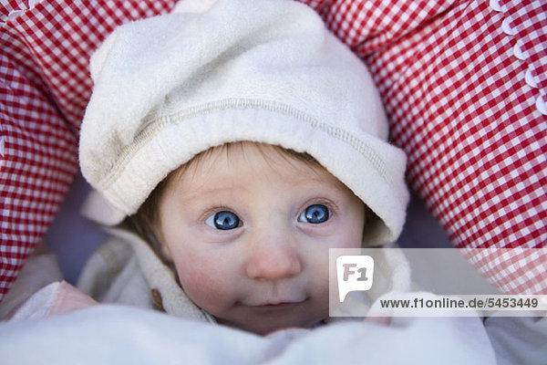 Ein Baby  das ein Kapuzenshirt trägt und nach oben schaut.