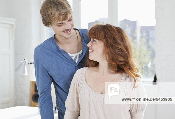 Eine junge Frau schaut zu ihrem Freund auf  der hinter ihr steht.