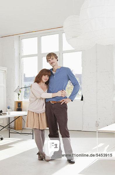 Ein junges Paar steht Seite an Seite mit den Armen umeinander.