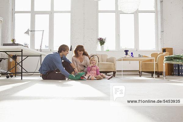 Eine junge  hippe Familie spielt zusammen auf dem Wohnzimmerboden.