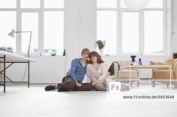 Ein junges Paar sitzt Seite an Seite auf dem Boden.