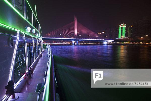 Yacht auf dem Pearl River in Hongkong und beleuchtete Haiyin Bridge im Hintergrund