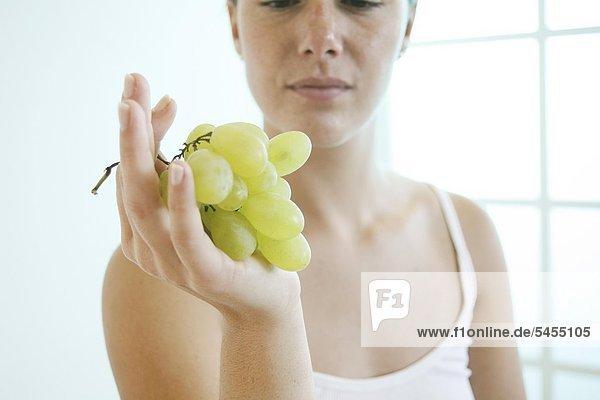 Junge Frau hält ein Bündel Trauben.