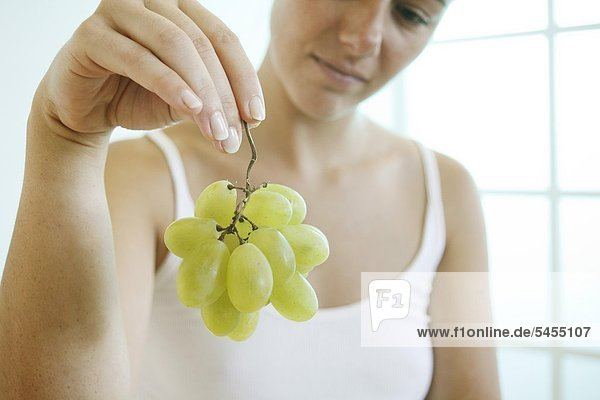 Frau hält ein Bund Weintrauben