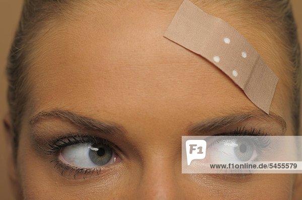 Junge Frau mit Pflaster auf der Stirn