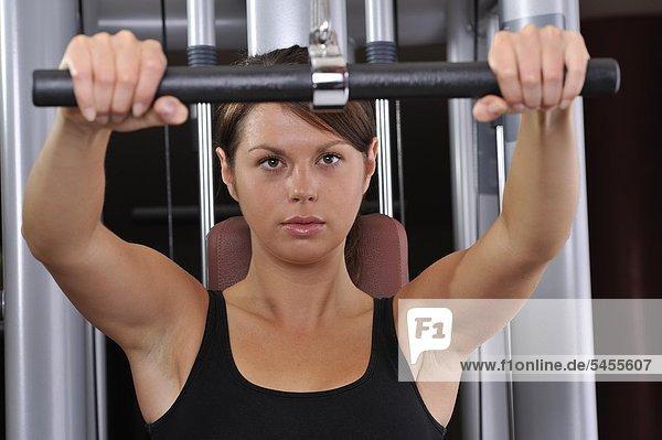 Junge Frau trainiert in einem Fitnessstudio