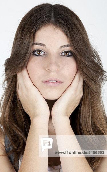 Junge Frau stützt Gesicht in Hände  Portrait