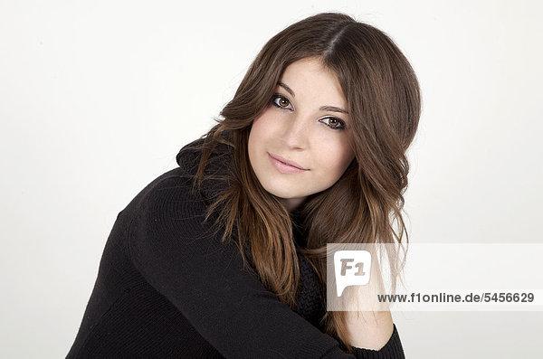 Junge Frau mit langen Haaren und schwarzem Pullover  Porträt