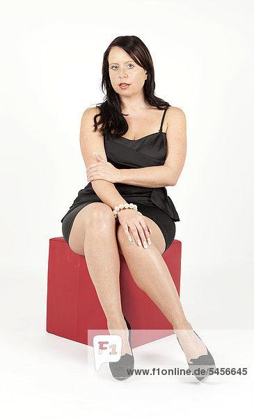 Junge Frau im schwarzen Abendkleid sitzt auf rotem Sitzwürfel