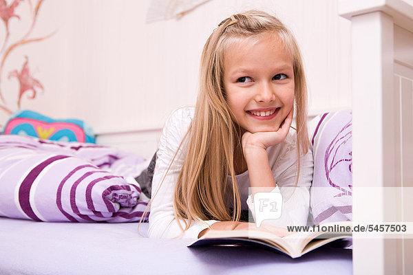 Mädchen liest in einem Buch  liegt im Bett
